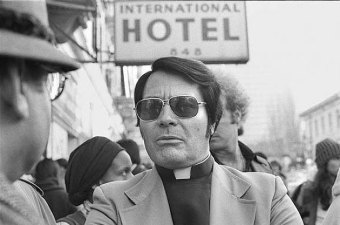 "Reverend Jim Jones standing outside of the International Hotel. The location and date are unknown. This photograph was taken from ""The Weblog of J. Max Wilson"" at https://www.sixteensmallstones.org/dont-drink-the-kool-aid-jonestown-was-an-atheist-marxist-socialist-cult/"