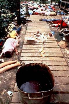 "Bodies of members of the Peoples Temple who died after their leader Jim Jones ordered them to drink a cyanide-laced beverage. The vat that contained the poison is in the foreground. This photograph was located on britannica.com in ""Jonestown Massacre""."