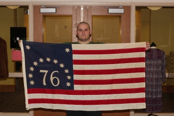 Student worker, Josh Knecht, holding a American Bicentennial flag from the Ken McCutchan collection, 1976. Credit: James Wethington