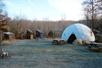 View of Ecovillage Training Center with geodesic dome (right), two solar heated showers (left center), and organic garden at rear in Lawrence County, Tenn., 2002. (Source: Don Janzen collection, CS 662, 070pc-0003)