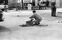 Man gathering debris from a mangled automobile and putting it into a box for investigation purposes. Given the location, date, and shape of the car, this is most probably the murder of Ray Ryan, a man in the oil business and a gambler. He went to his health club (Olympia Health and Beauty Resorts, Inc. at 4920 Bellemeade Ave.) the morning of Oct. 18, 1977, and when he came out and started his car, it exploded. The murder was not solved, but is widely believed to have been a mob hit., October 8, 1977. Source: University Archives and Special Collections, MSS 034-1728.