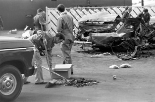 Man sweeping and shoveling debris from an automobile and putting it into a box for investigation purposes. Next to him is an Evansville Fire Department employee, and other law enforcement officials are nearby, some inspecting the mangled remains of the car. Given the location, date, and shape of the car, this is most probably the murder of Ray Ryan, a man in the oil business and a gambler. He went to his health club (Olympia Health and Beauty Resorts, Inc. at 4920 Bellemeade Ave.) the morning of Oct. 18, 1977, and when he came out and started his car, it exploded. The murder was not solved, but is widely believed to have been a mob hit, 1977. Source: University Archives and Special Collections, MSS 038-1729.