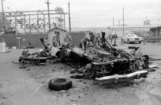 Officials/investigators inspect the mangled remains of a car behind the electric substation on Bellemeade Ave., near the Hale & Sons Auto Parts store, Lawndale Branch, at 5009 Bellemeade Ave. Given the location, date, and shape of the car, this is most probably the murder of Ray Ryan, a man in the oil business and a gambler. He went to his health club (Olympia Health and Beauty Resorts, Inc. at 4920 Bellemeade Ave.) the morning of Oct. 18, 1977, and when he came out and started his car, it exploded. The murder was not solved, but is widely believed to have been a mob hit., 1977. Source: University Archives and Special Collections, MSS 038-1732.