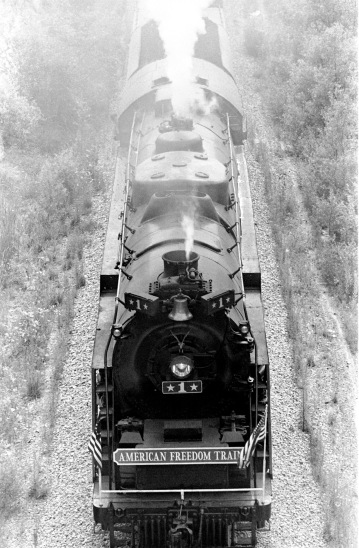 "Looking down on the American Freedom Train, steaming down the tracks. ""The triumph of the steam-powered American Freedom Train was, indeed, the only nationwide celebration of the Bicentennial. It was pulled by steam locomotives in the age of the diesel, and would improve on the three display cars of its predecessor, the 1947 Freedom Train. The American Freedom Train would feature twelve display cars, ten that visitors would go aboard and pass through and two to hold large objects that would be viewed from the ground through huge ""showcase"" windows. The display cars were filled with over 500 precious treasures of Americana. Included in these diverse artifacts were George Washington's copy of the Constitution, the original Louisiana Purchase, Judy Garland's dress from The Wizard of OZ, Joe Frazier's boxing trunks, Martin Luther King's pulpit and robes, and even a rock from the moon. The American Freedom Train (AFT) was a 26-car train led by one of three enormous steam engines restored just for the occasion. Over a 21 month period from April 1, 1975 to December 31, 1976 more than 7 million Americans visited the train during its tour of all 48 contiguous states. Tens of millions more stood trackside to see it go by."" (http://www.freedomtrain.org/american-freedom-train-home.htm) The Freedom Train's only visit to Evansville was June 15-17, when it was parked behind the Civic Center/Vanderburgh Auditorium at 715 Locust St. in Evansville, Indiana, 1976. Source: Gregory Smith Collection, MSS 034-0604."