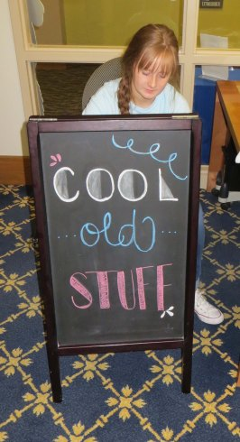 "Student assistant, Mikayla Hanks, creating the ""Cool Old Stuff"" sign for the archives department, 2018."