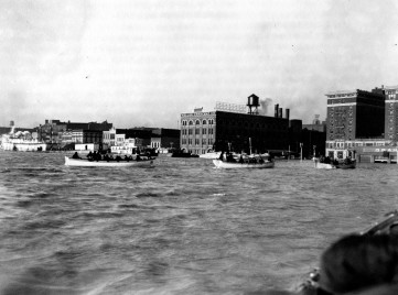 U.S. Coast Guard cutters on Dress Plaza, approaching the city. Steamboat and barges beyond them. Identifiable buildings are Keller Crescent Printing & Engraving Co. at 24-28 SE Riverside Dr., Hotel McCurdy at 101-11 SE 1st St., and in front of the hotel, the Graham Motor Cars distributorship owned by Robert W. Baskett at 118 SE Riverside Drive, 1937. Source: Flood of 1937 collection (MSS 272-0765)