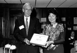 Byron Wright giving Mary Lue Ruessler, secretary of Business Affairs, her certificate of appreciation, n.d. Source: University Photographs 02663.