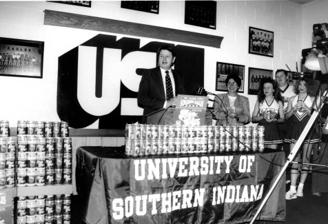 (Left to Right): Dr. H. Ray Hoops, Sherrianne Standley, and USI cheerleaders introducing Screaming Eagles soda, 1995. Source : University Archives and Special Collections, UP 05305.