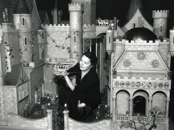 Colleen Moore in her Fairy Castle, holding Cinderella's coach.