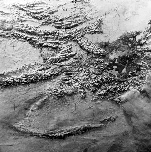 A near vertical view of the snow-covered northwest corner of Wyoming as seen from the Skylab space station in Earth orbit. A Skylab 4 crewman used a hand-held 70 mm Hasselblad camera to take this picture. A small portion of Montana and Idaho is in this photograph. The dark area is Yellowstone National Park. The largest body of water is Yellowstone Lake. The Absaroka Range is immediately east and northeast of Yellowstone Lake. The elongated range in the eastern part of the picture is the Big Horn Mountains. The Wind River Range is at bottom center. The Grand Teton National Park area is almost straight south of Yellowstone Lake. Approximately 30% of the State of Wyoming can be seen in this photograph, 1974. Source: Lee William Jones collection, MSS 244-0255.