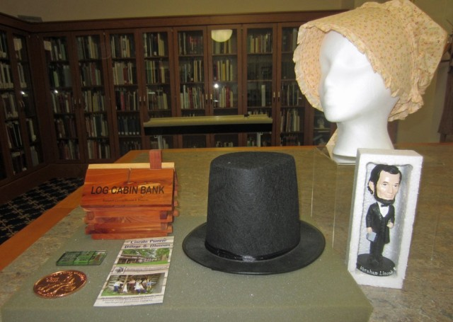 Commemorative Lincoln penny, magnet, log cabin bank, brochure, top hat, pioneer bonnet, and Lincoln bobble-head, n.c.