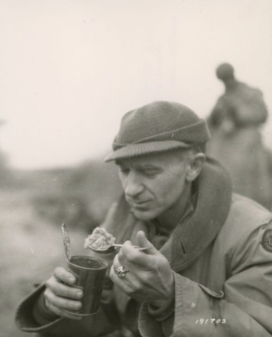 "Pyle eating ""C"" rations in the Anzio Beachhead area, Italy, in March 18, 1944. Source: https://bit.ly/2QTEFbR"