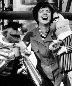 Joan Ganz Cooney sharing a laugh with                               Ernie and Bert. Source: https://muppet.fandom.com/wiki/Sesame_Street