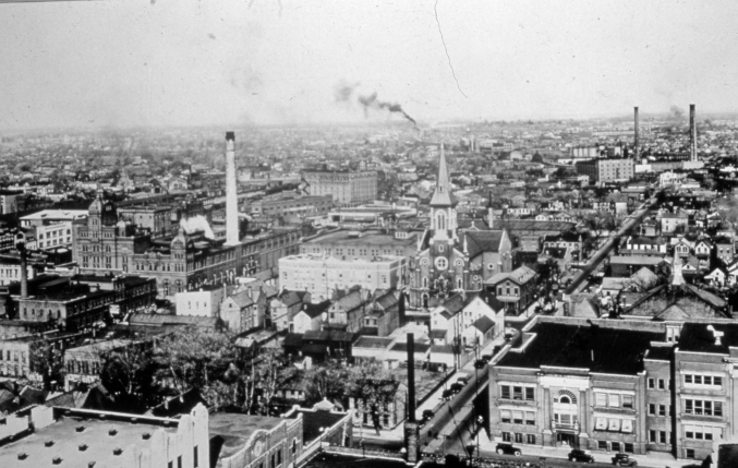 This 1920s image, looking down on the central part of Evansville, gives some idea of what had to be removed for the Civic Center to be built. The smokestack just left is center is Cook Brewery, and the church in the center is Assumption Catholic Church. Both were razed for the Civic Center. Source: Darrell Bigham Collection MSS 181-1271.