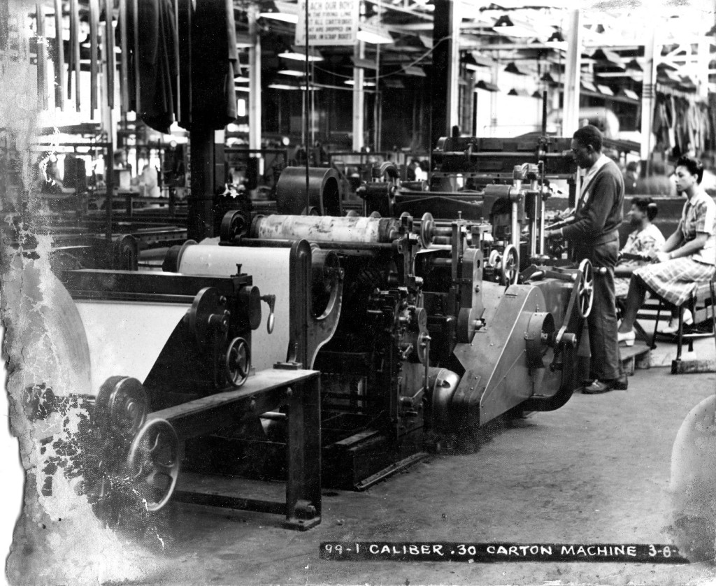 African American man and women working at a 30--caliber carton machine. MSS 253-254