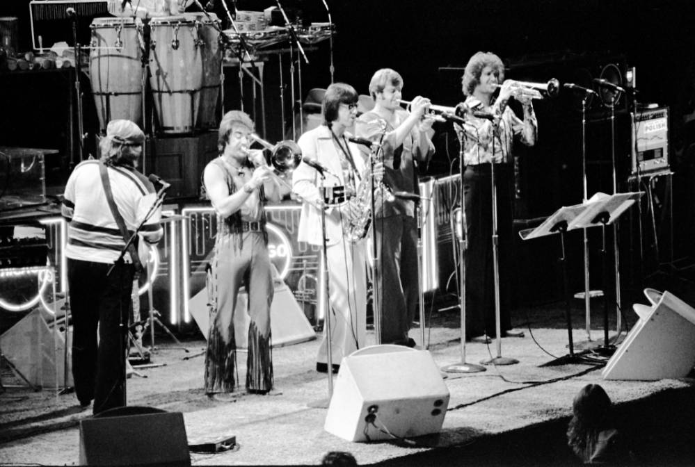 Cross view of guitarist and brass and woodwind players, in the band Chicago, 1976.