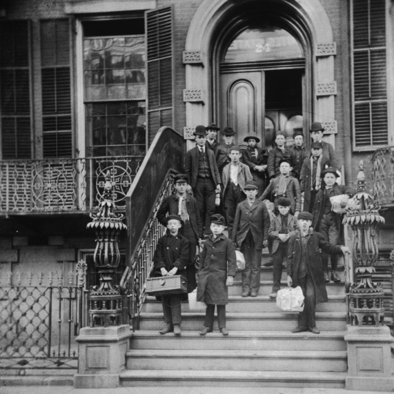 A group outside of the Children's Aid Society's central office in New York City. The children hold satchels with their belongings as they prepare to travel west, c. 1895. Source: https://bit.ly/3zUbquO